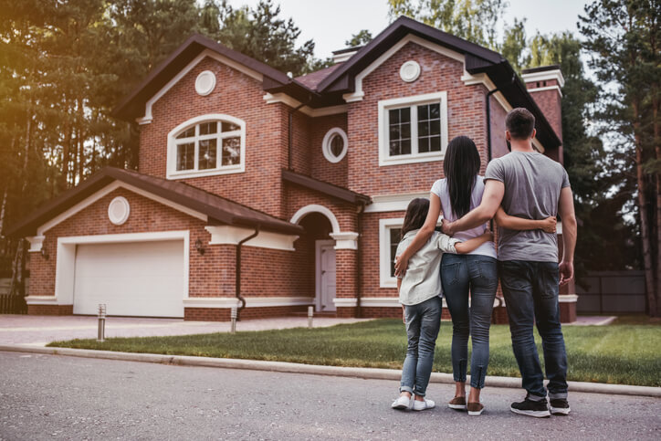A family standing in front of the house that they need to sell fast.